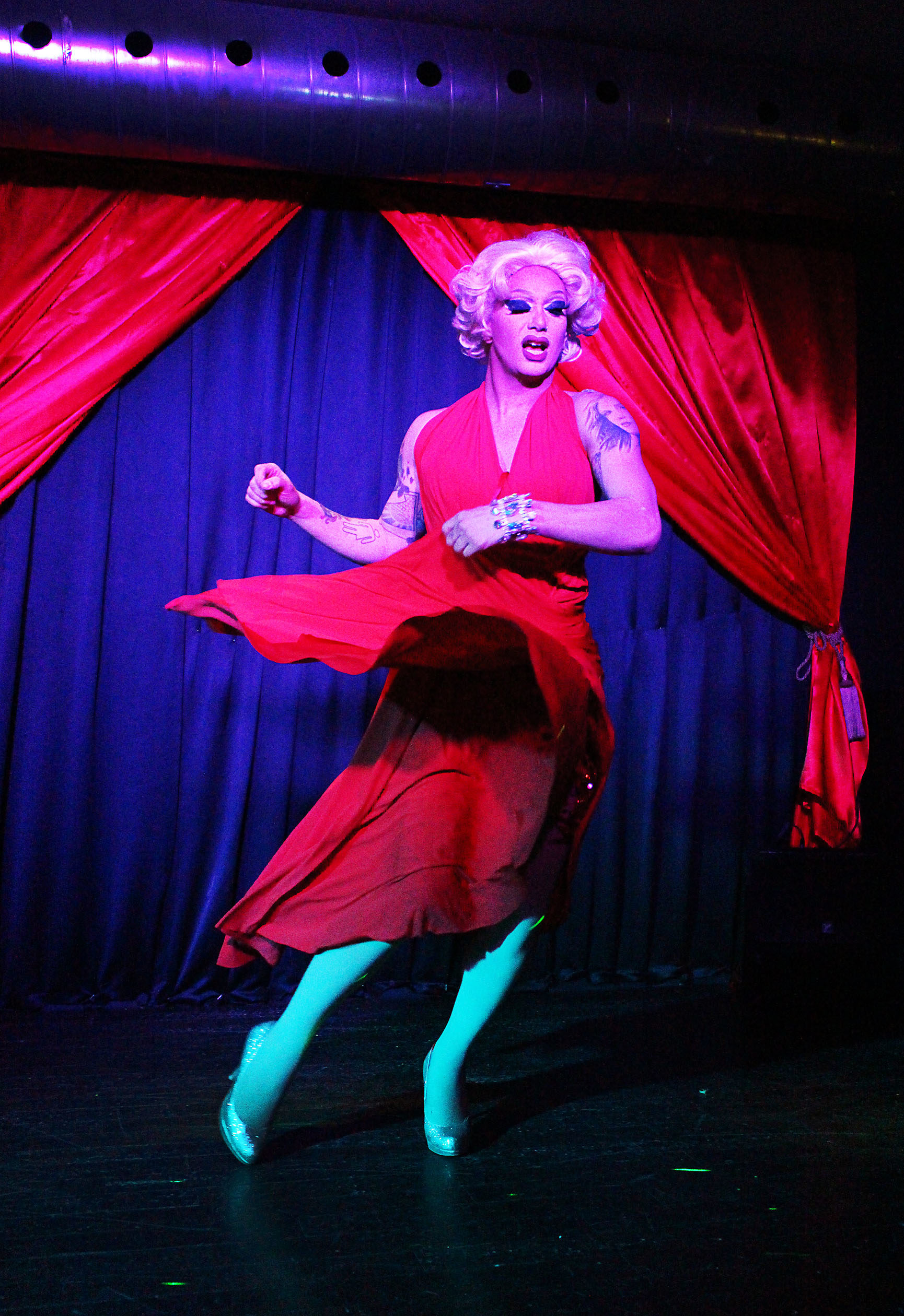 Scarlett Bobo performing on stage in a red outfit, with red curtains in the background.