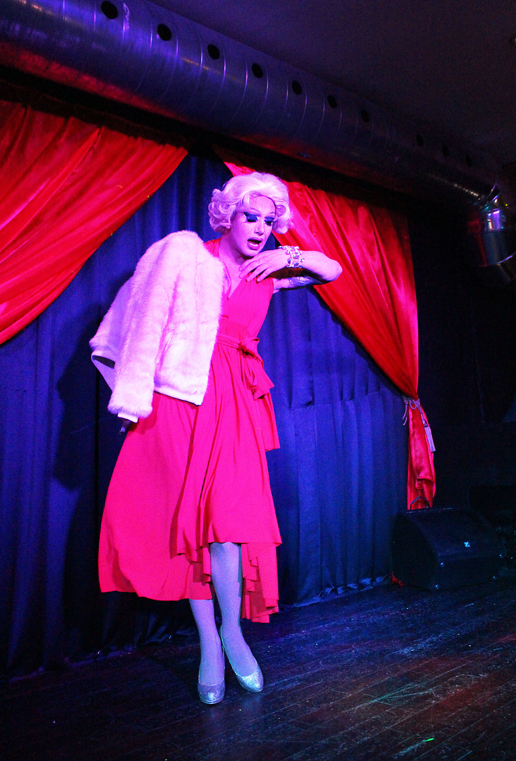 Scarlett Bobo on stage in a red outfit, holding a furry pink sweater, with red curtains in the background.