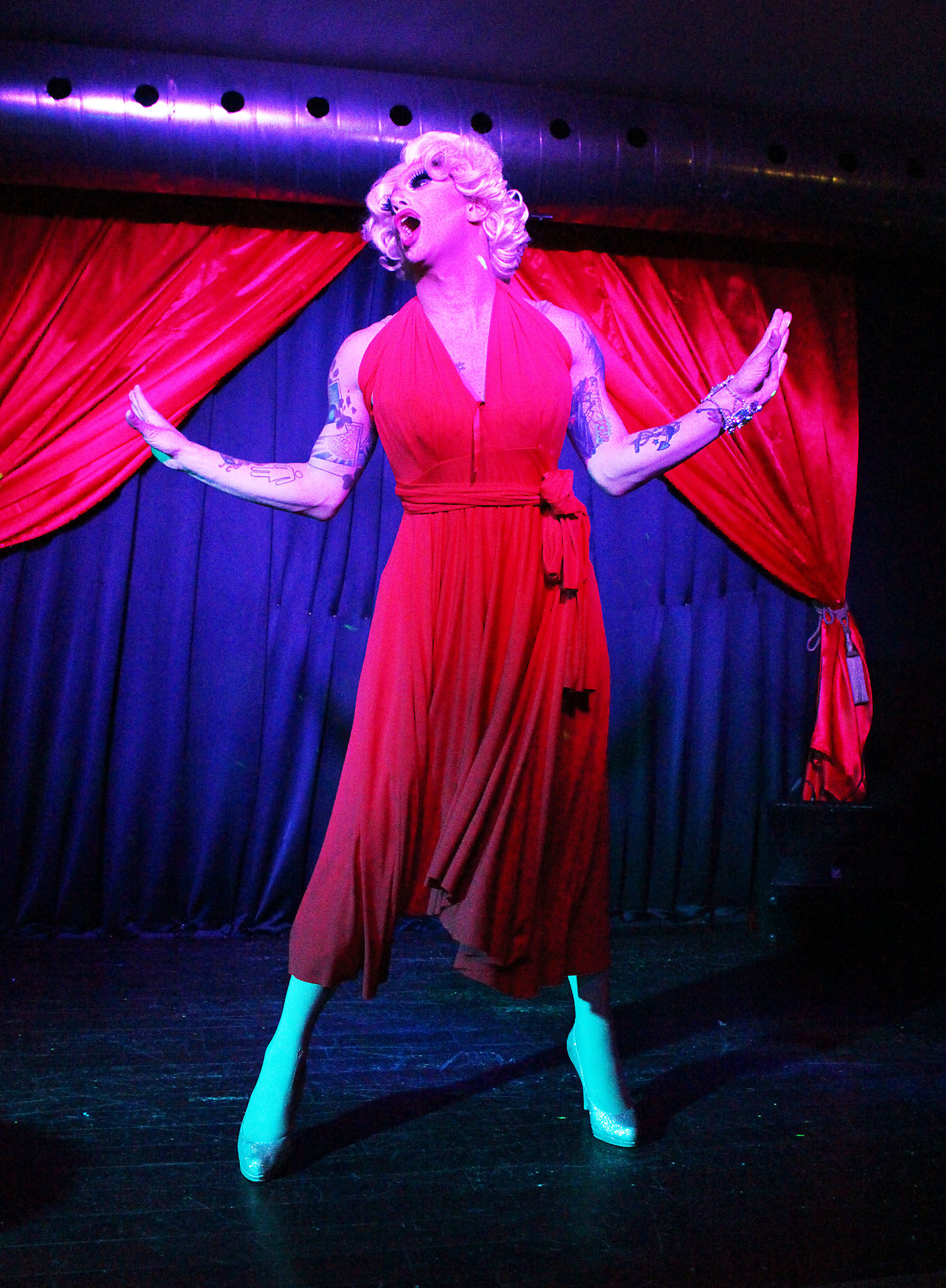 Scarlett Bobo on stage in a red outfit, with red curtains in the background.