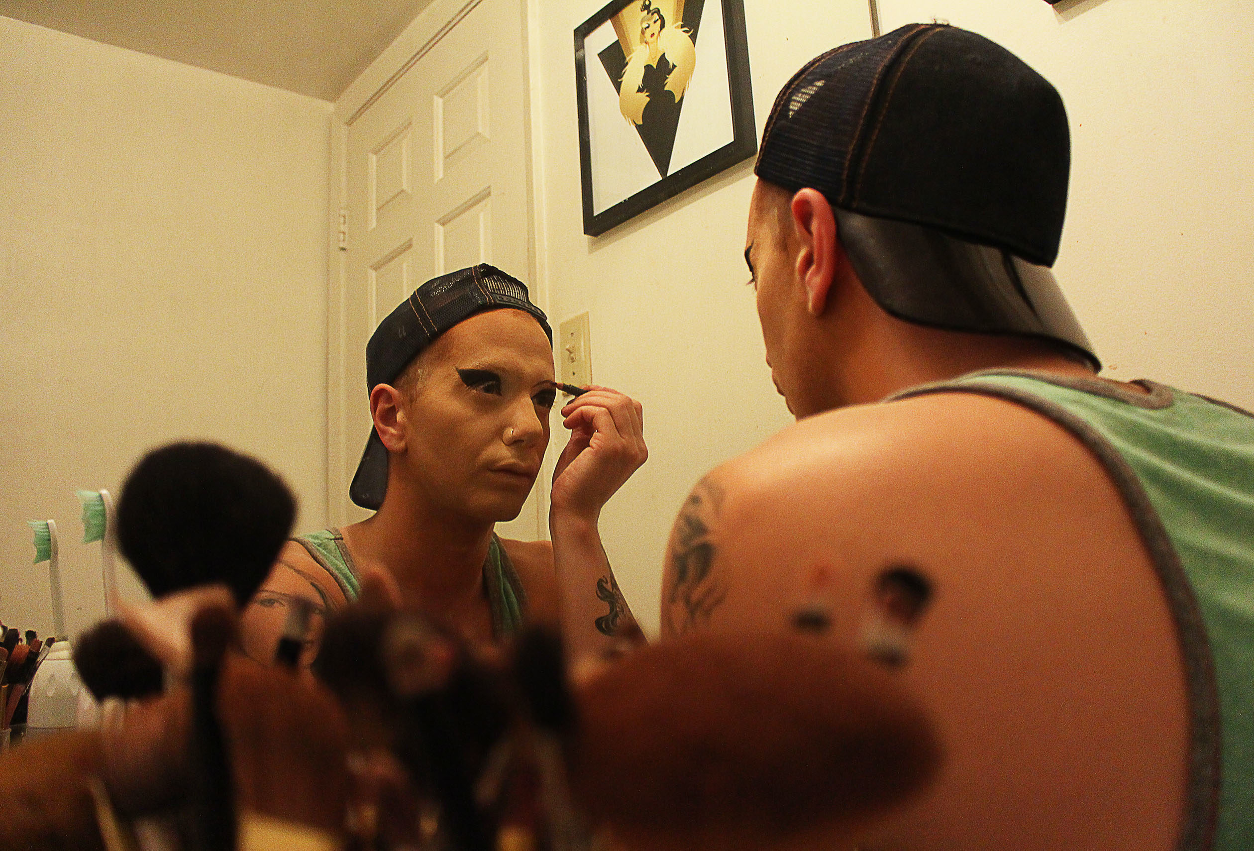 Matty Cameron applying makeup in the mirror, with brushes visible in the left corner of the photo.