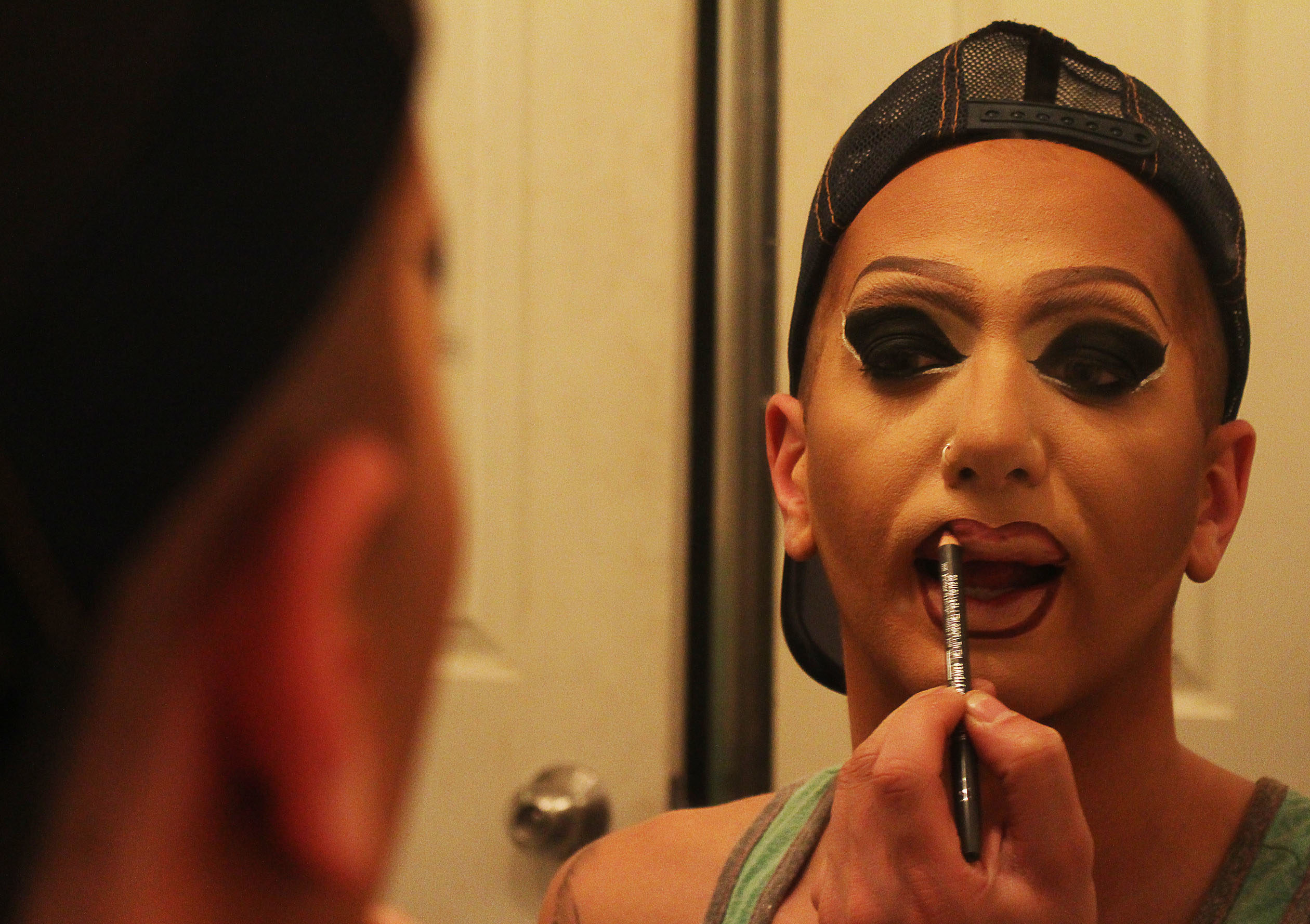 Matty Cameron applying makeup in the mirror.