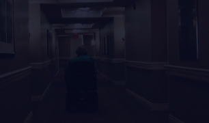 A photo of a person in a wheelchair, moving down a hallway. The photo has a dark overlay over it.