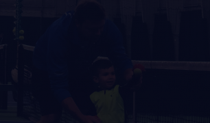 A photo of an adult and child in front of a tennis net, with the child holding a tennis ball. There is a dark overlay over the image.