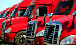 A series of red trucks are lined up, parked.